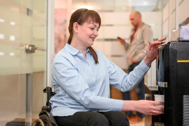 Confident businesswoman in wheelchair pouring water