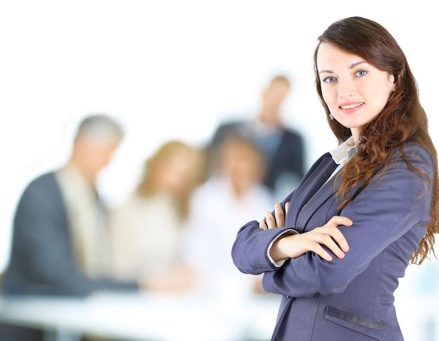 Confident businesswoman with team behind her