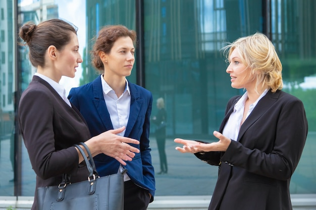 Confident businesswomen discussing project emotionally outdoors. business colleagues wearing suits standing together in city and talking.