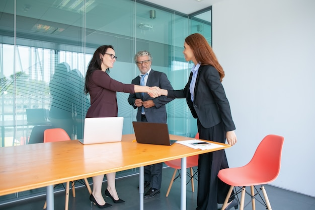 Уверенные деловые женщины, рукопожатие и приветствие друг друга