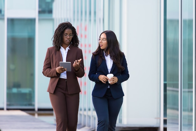 Confident businesswomen walking with tablet