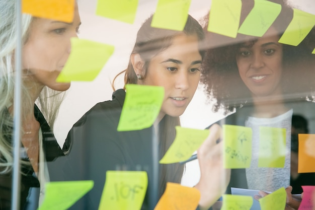 Confident businesswomen writing notes on stickers for startup. successful experienced managers in suits meeting in conference room and planning strategy. teamwork, business and management concept