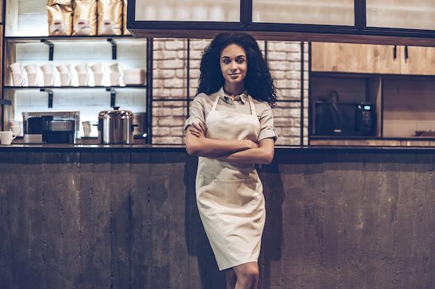 Уверенный владелец кафе. молодая веселая африканская женщина в фартуке, скрестив руки и глядя в камеру с улыбкой, стоя у барной стойки
