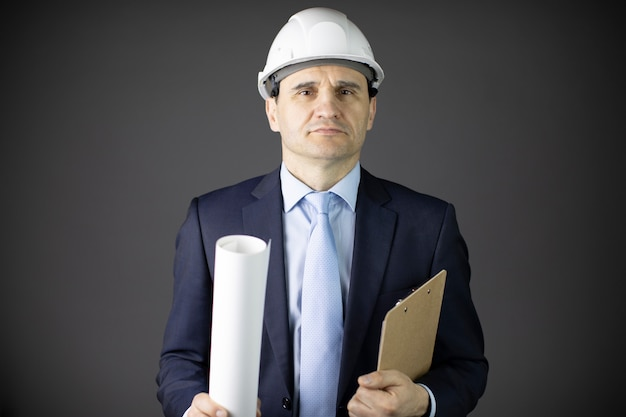Confident and calm builder in white helmet holds rolled-up drawing and clipboard