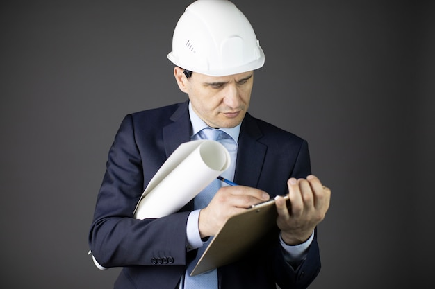 Confident and calm handsome engineer wearing white helmet writes on clipboard