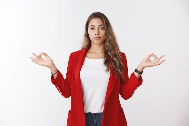 Уверенно спокойная современная успешная бизнесвумен, сдерживающая чувства, показывая жест мудры позы лотоса, мирно, без стресса, медитируя, стоя в нирване, белая стена в офисе