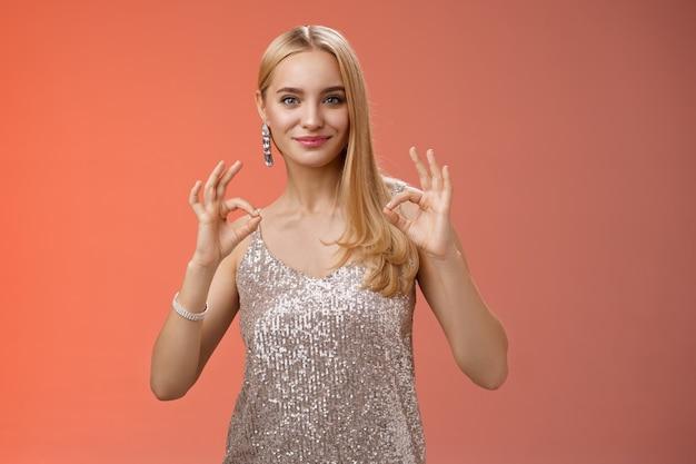 Уверенная беззаботная оптимистичная молодая белокурая женщина уверяет, что все сделано идеально, нравится результат шоу, хорошо, хорошо, без проблем, жест улыбается, самоуверенно стоит, серебряное роскошное платье, красный фон.