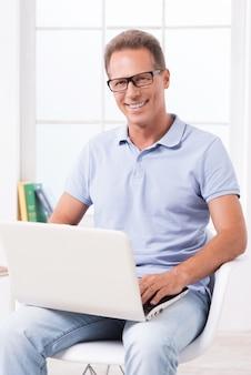 Уверенно случайный бизнесмен. уверенный зрелый мужчина работает на ноутбуке и улыбается, сидя на стуле