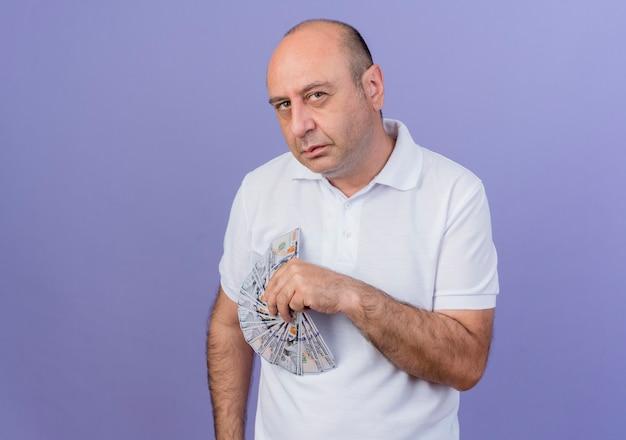 Уверенный случайный зрелый бизнесмен, держащий деньги, смотрящий в камеру, изолированный на фиолетовом фоне с копией пространства