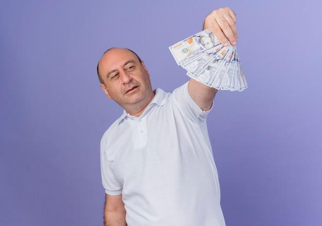 自信を持ってカジュアルな成熟したビジネスマンが伸びて、コピースペースで紫色の背景に分離されたお金を見て