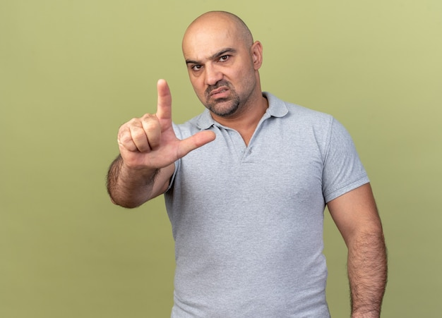 Confident casual middle-aged man doing loser gesture isolated on olive green wall