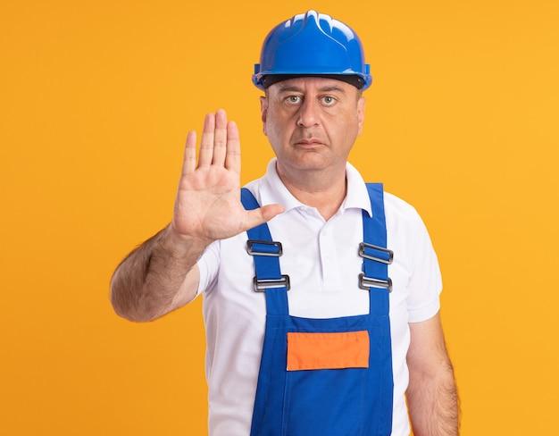Уверенный кавказский взрослый человек-строитель в форме жестов стоп знак рукой на оранжевом