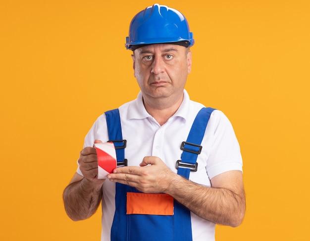制服を着た自信を持って白人の大人のビルダーの男はオレンジ色のスコッチテープを保持します