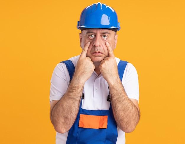 제복을 입은 자신감 백인 성인 작성기 남자가 오렌지에 눈꺼풀을 당깁니다.