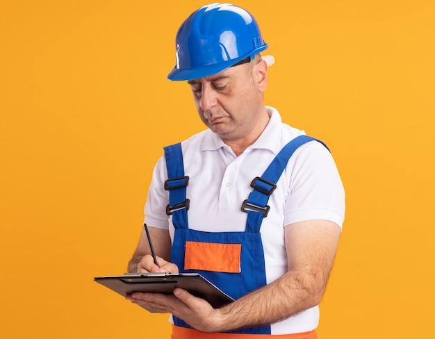 制服を着た自信のある白人の大人のビルダーの男は、オレンジ色の鉛筆でクリップボードに書き込みます