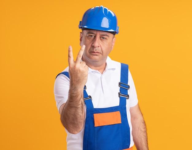 Uomo adulto caucasico fiducioso del costruttore in gesti uniformi due con il dito sull'arancio