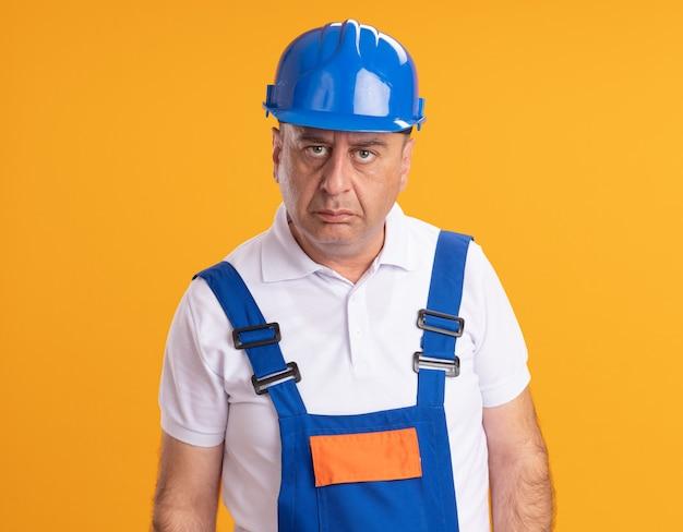 L'uomo adulto caucasico sicuro del costruttore in uniforme esamina la macchina fotografica sull'arancio