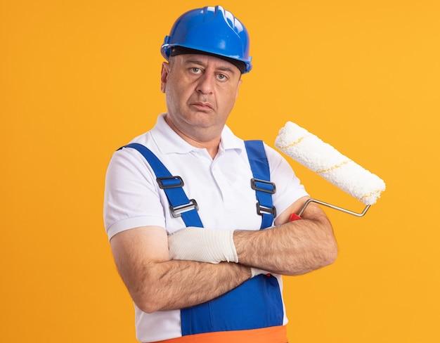 Fiducioso uomo caucasico adulto costruttore in uniforme si leva in piedi con le braccia incrociate tenendo la spazzola a rullo sull'arancio