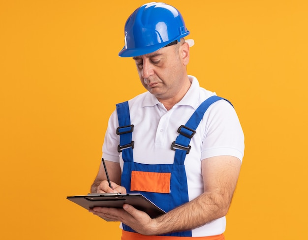 L'uomo adulto caucasico sicuro del costruttore in uniforme scrive negli appunti con la matita sull'arancio