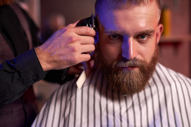 Confident caucasian barber mster cuts hair and beard of men in the barbershop