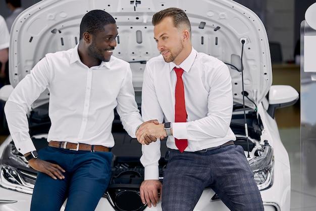 Confident caucasian dealer or salesman shaking hands to customer in dealership