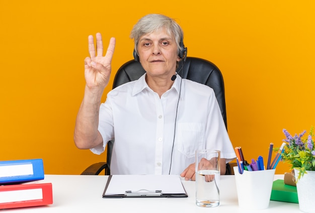 Confident caucasian female call center operator on headphones sitting at desk with office tools gesturing three with fingers