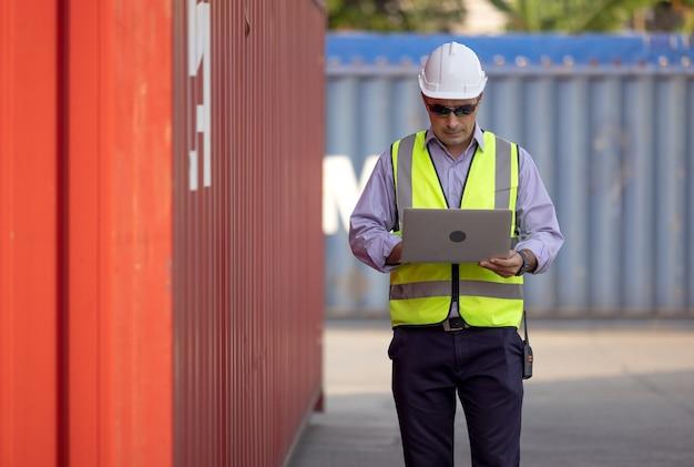 Уверенный кавказский инженер-мужчина в белом защитном шлеме, использующий компьютерный ноутбук и проверяющий для контроля загрузочную коробку контейнеров с грузового грузового корабля для импорта и экспорта, транспорта