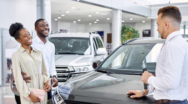 自動車販売店で車を販売する自信を持って白人男性の販売員
