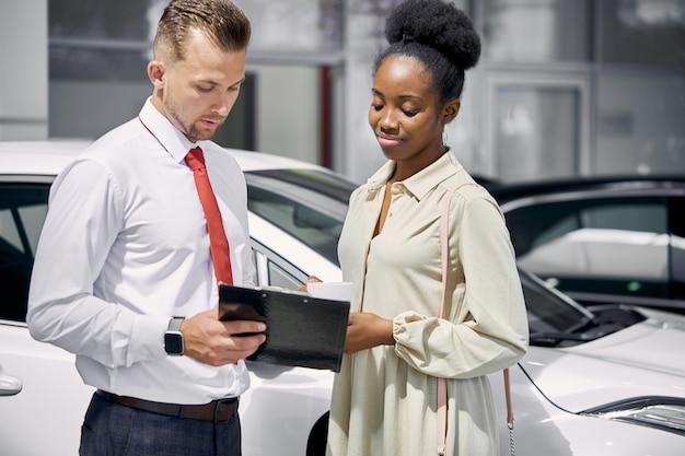 자동차 대리점에서 자동차를 판매하는 자신감 백인 남자 판매원