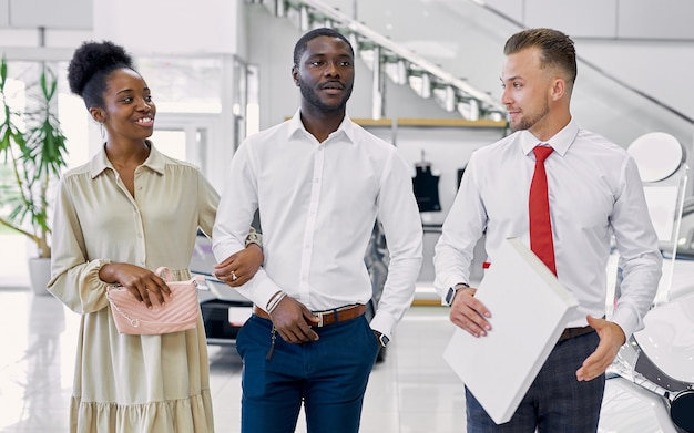 Confident caucasian man salesperson selling cars at car dealership