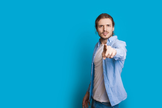 Уверенный кавказский мужчина с длинными волосами и бородой, указывая, позирует на синей стене со свободным пространством