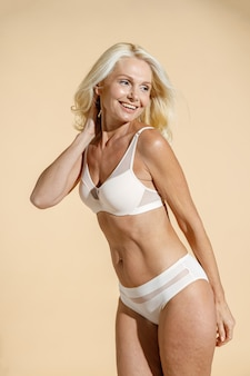 Confident caucasian mature blonde female model with fit body in white lingerie smiling aside posing