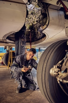 Confident caucasian mechanic working at an airplane hangar and fixing the landing gear of a plane