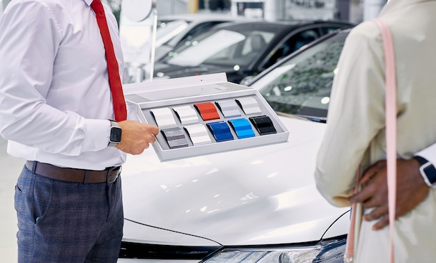 Confident caucasian professional consultant show colour palette of cars to customers