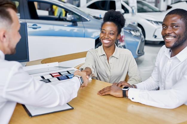 自信を持って白人のプロのコンサルタントが顧客に車のカラーパレットを表示します