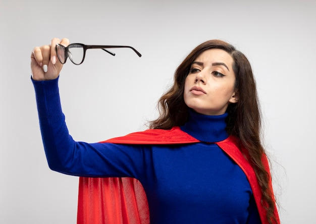 Confident caucasian superhero girl with red cape holds and looks at optical glasses on white