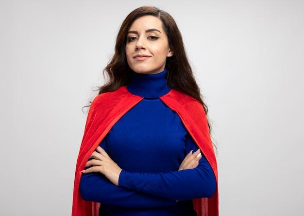 Уверенная кавказская девушка-супергерой в красном плаще стоит со скрещенными руками, изолированными на белой стене с копией пространства