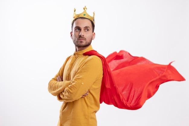 Fiducioso uomo caucasico supereroe in occhiali ottici con corona e mantello rosso sta lateralmente con le braccia incrociate crossed