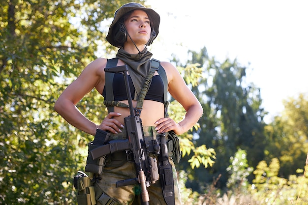 Confident caucasian woman in soldier wear looking for enemy, portrait of slim woman in top