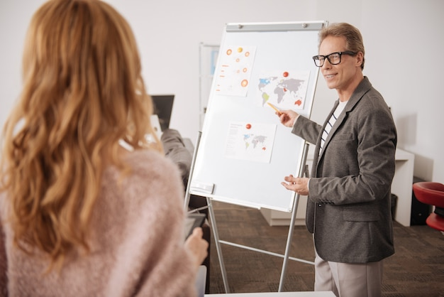 Confident charismatic smart businessman standing near the white board in the office and pointing on it while representing the project to the colleagues