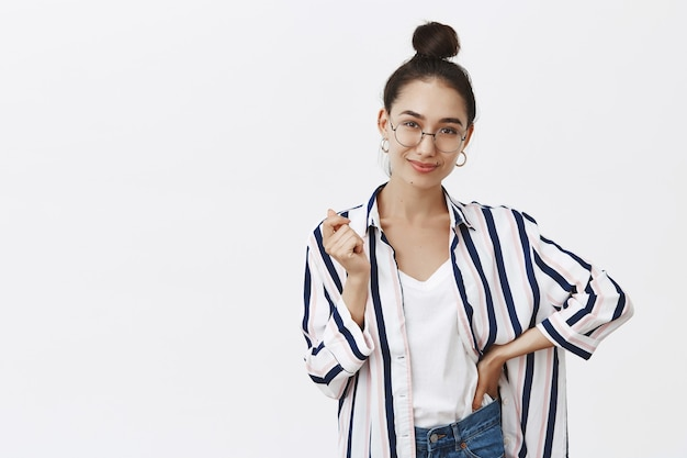 Confident charming female in glasses and shirt with bun hairstyle, gesturing with hand and holding palm on waist, smirking, being self-assured and happy