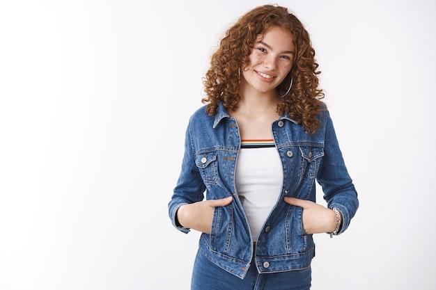 自信を持って魅力的な赤毛のガールフレンド20代のデニムジャケットを着て散歩に出かける手を握るポケットを広く笑って友達に会う小さな話通り立っている白い背景が楽しくニヤリと笑う