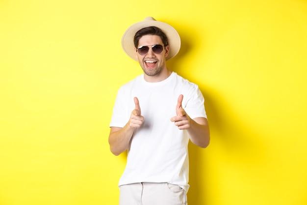 Ragazzo fiducioso e sfacciato in vacanza che flirta con te, puntando il dito alla telecamera e strizzando l'occhio, indossando un cappello estivo con occhiali da sole, sfondo giallo