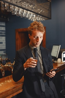 Fiducioso uomo allegro seduto al bancone del bar, bere birra e networking su smartphone.