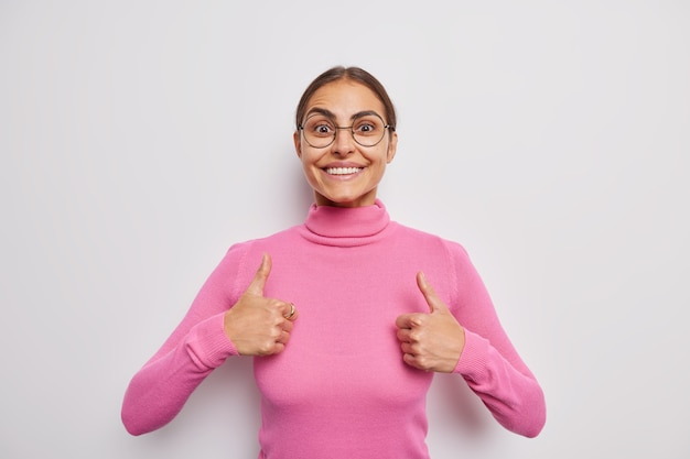 Confident cheerful woman with dark hair smiles pleasanty keeps thumbs up does positive gesture happy for success says very good praises work approves and agrees likes something poses indoor