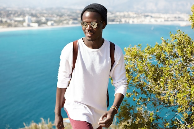 Confident cheerful young black european male student wearing trendy eyewear and hat hiking in mountain above azure sea, showing his friends beauties and landmarks of his native town at seaside