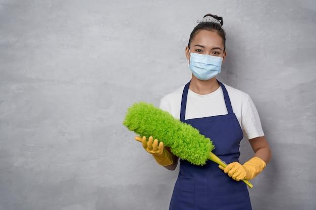 黄色のゴム手袋とマイクロファイバーダスターを保持している医療マスクを身に着けている自信を持って掃除をする女性