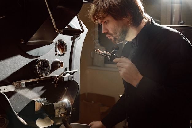 Confident coffee roaster man is checking preparation process