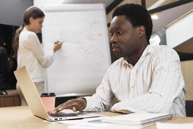 Uomo africano concentrato fiducioso utilizzando gadget elettronici portatili alla scrivania in ufficio