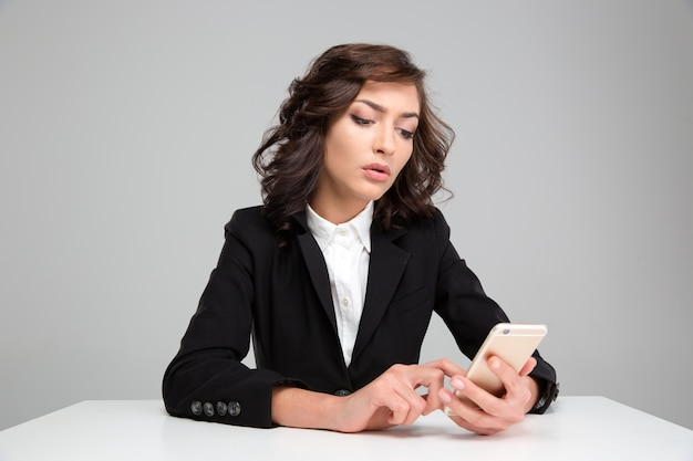 Confident concentrated beautiful curly young woman in black jacket sitting and using cellphone
